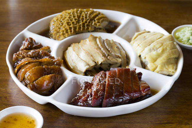 Various chinese meals on portioned plate — Stock Photo