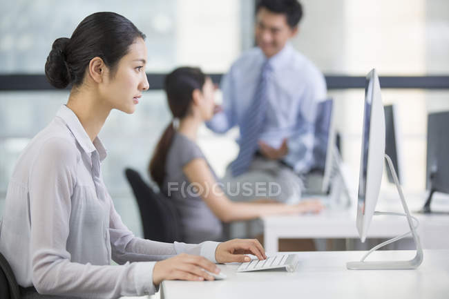 Chinese businesswoman using computer in office — Stock Photo