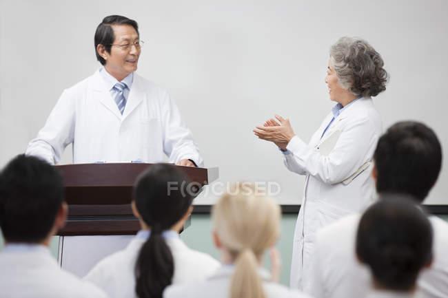 Medical workers clapping at seminar to senior man — Stock Photo