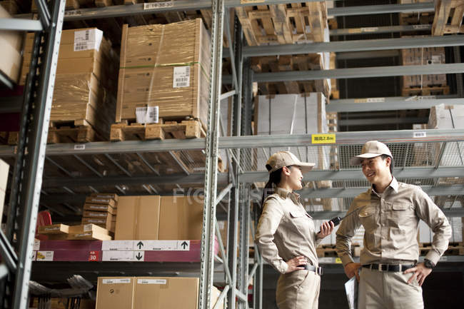 Male and female Chinese workers talking in warehouse — Stock Photo