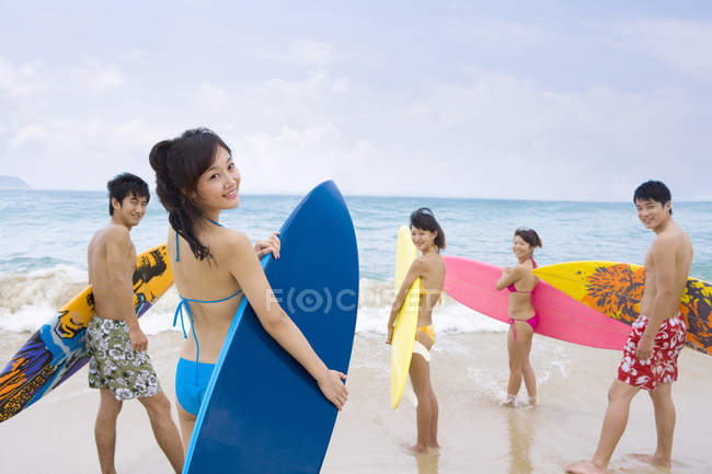 Chinese friends standing with surfboards on Hainan beach — Stock Photo