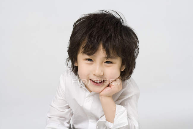 Portrait of little Asian boy with hand on chin on gray background — Stock Photo