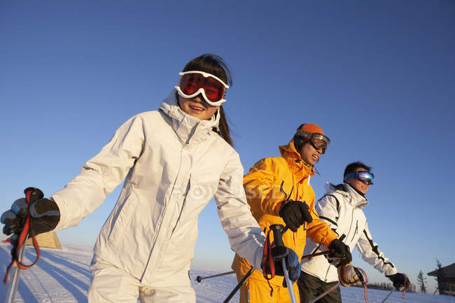 Chinese people posing with ski equipment at slope — Stock Photo