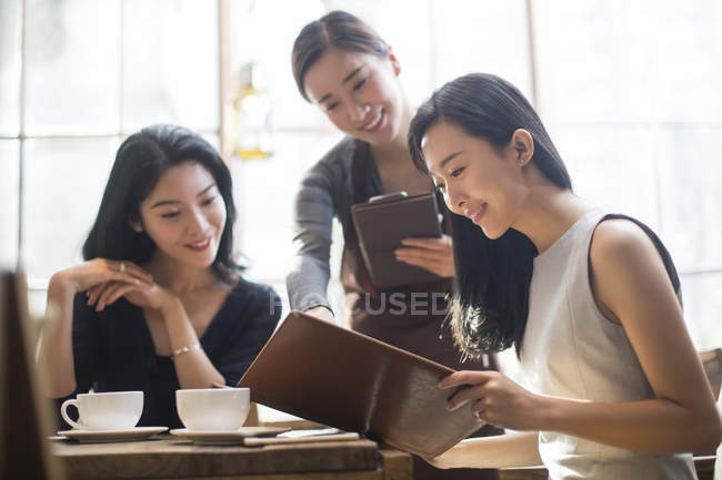Chinese female friends ordering with waitress in cafe — Stock Photo