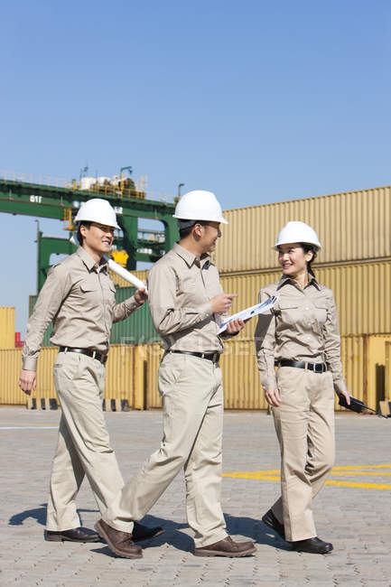 Chinese shipping industry workers talking in harbor — Stock Photo
