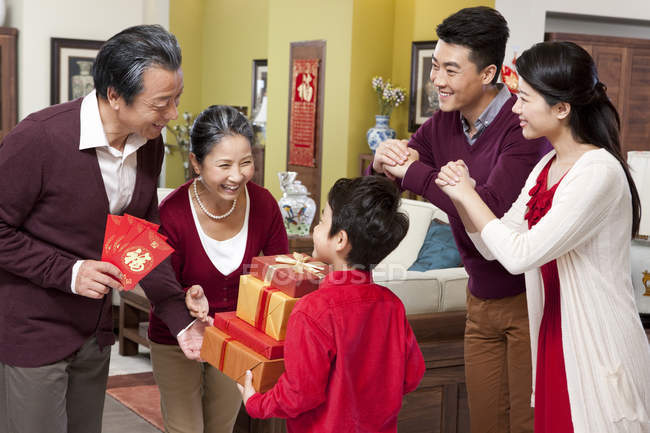 Little boy with parents visiting grandparents with gifts during Chinese New Year — Stock Photo
