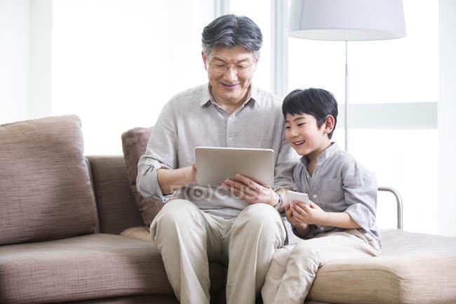 Китайський діда і онука, використовуючи цифровий планшет на дивані — стокове фото