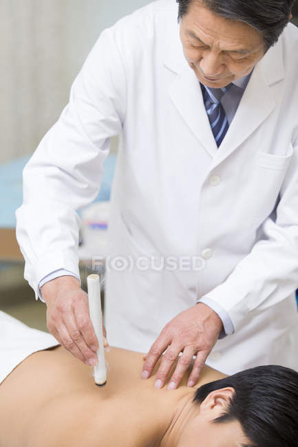 Senior chinese doctor giving moxibustion therapy to male patient — Stock Photo