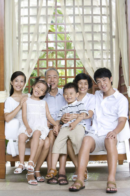 Portrait of Chinese family with siblings sitting on bench on vacation — Stock Photo