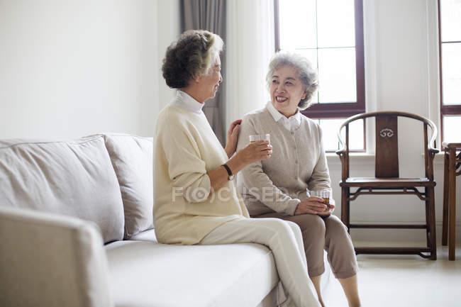 Senior Chinese women talking with tea on sofa — Stock Photo