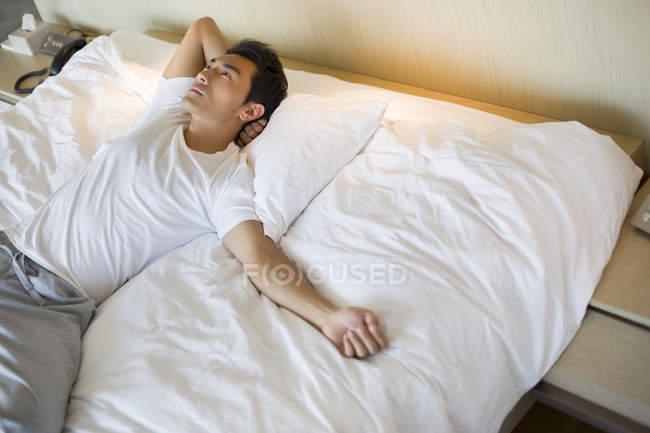 Китаец лежит на кровати и смотрит вверх — стоковое фото