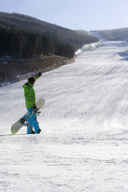 Snowboarder looking at view with arm outstretched — Stock Photo