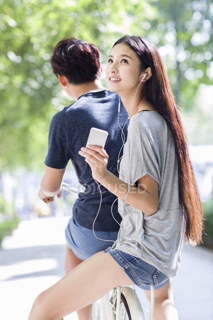 Chinese woman sitting with man on bicycle and listening to music — Stock Photo