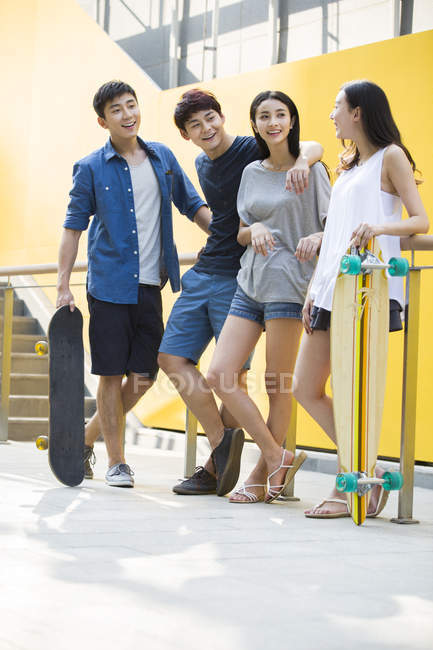Китайские друзья, холдинг скейтборды на улице — стоковое фото