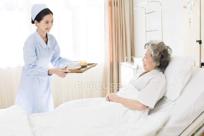 Enfermeira chinês serve comida para paciente sênior — Fotografia de Stock