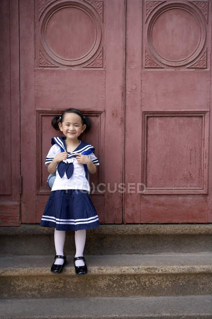 Chinese elementary age girl in school uniform leaning on door — Stock Photo