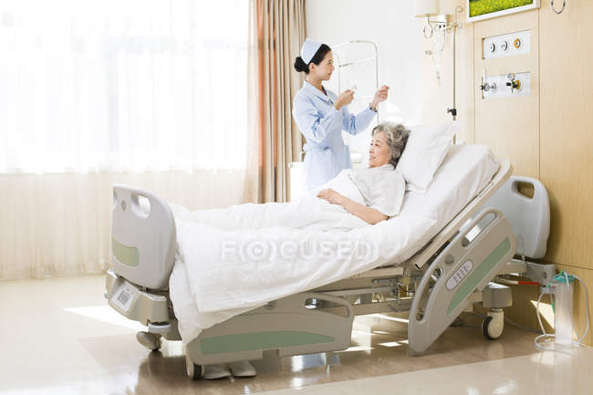 Infirmière chinoise changeant saline goutte à goutte en chambre senior femme — Photo de stock