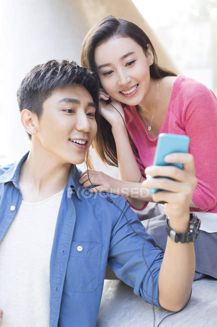 Chinese couple using smartphone together and listening music — Stock Photo