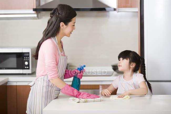Chine mère et fille nettoyage comptoir de cuisine avec vaporisateur bouteille — Photo de stock
