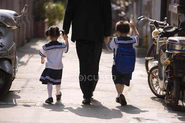 Отец держит детей за руки, идя по улице, вид сзади — стоковое фото