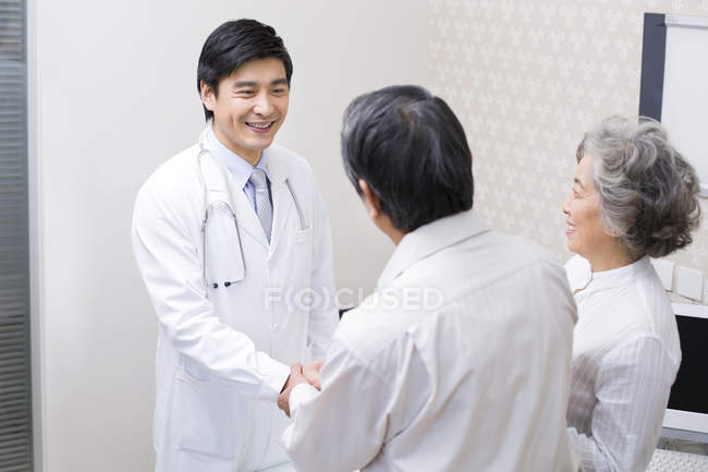 Chinese senior couple shaking hands with doctor in hospital — Stock Photo