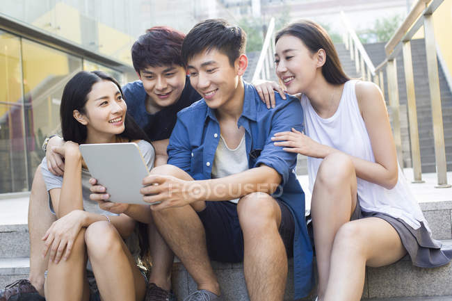 Chinese friends using digital tablet and looking down — Stock Photo