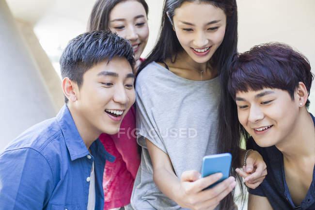 Amici cinesi guardando smartphone e sorridendo — Foto stock