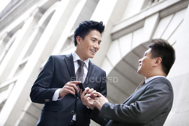 Colleghi d'affari cinesi con smartphone di fronte all'edificio — Foto stock