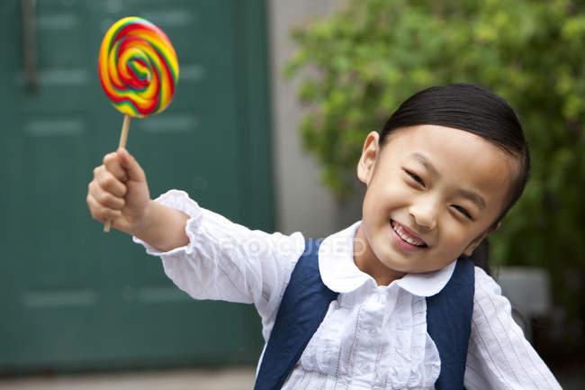 Écolière chinoise tenant sucette sur la rue — Photo de stock