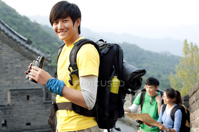 Hombre chino con prismáticos mirando en cámara con amigos en la Gran Muralla - foto de stock