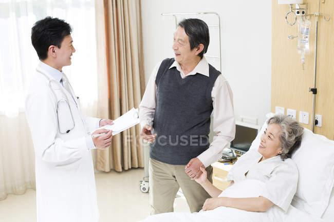 Médico chinês falando com casal sênior no hospital — Fotografia de Stock