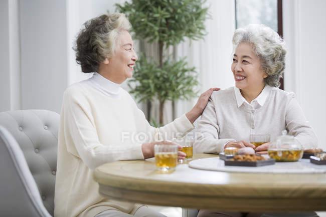 Senior Chinese women talking while drinking tea — Stock Photo