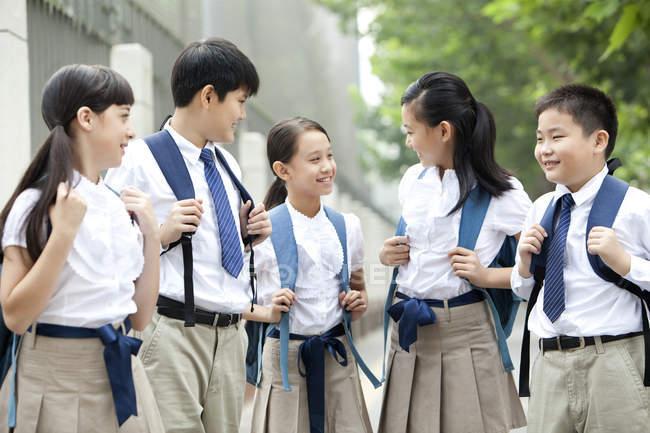 Cinese scolari in uniforme scolastica parlando su strada — Foto stock