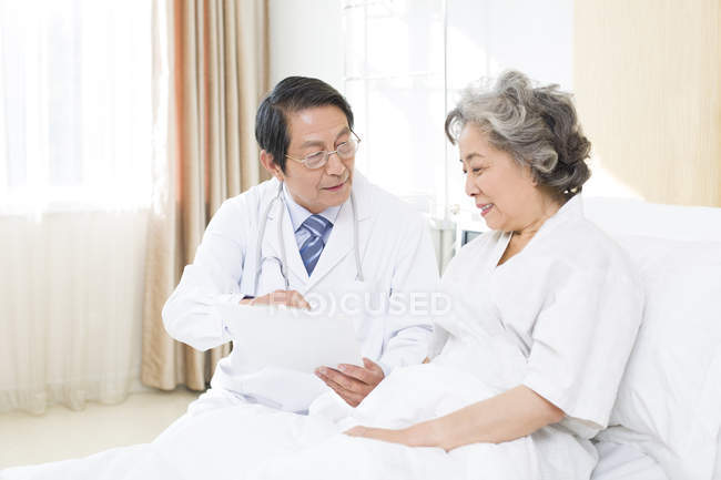 Chinese doctor showing medical record to patient in hospital — Stock Photo