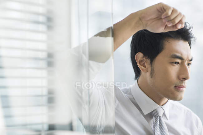 Chinesischer Geschäftsmann lehnt sich an Tür und blickt nach unten — Stockfoto