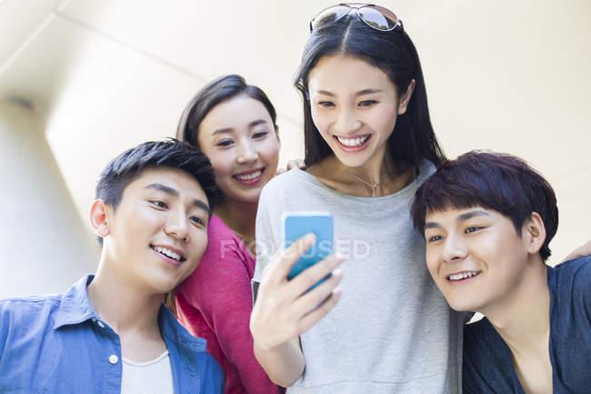 Chinesische Freunde schauen aufs Smartphone und lächeln — Stockfoto
