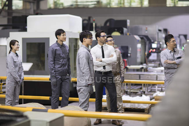 Confident businessman and engineering team looking away at factory — Stock Photo