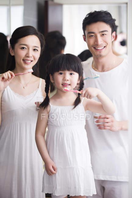 Famiglia cinese lavarsi i denti e guardando in macchina fotografica — Foto stock