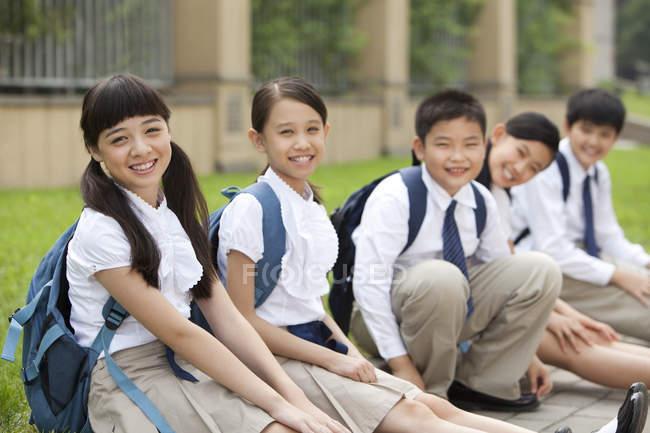 Китайские школьники сидят на полу в школьном дворе — стоковое фото