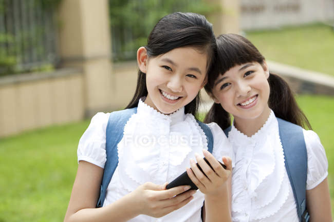 Chinese schoolgirls holding smartphone in school yard — Stock Photo