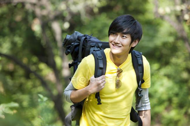 Turista chinês com mochila em madeiras — Fotografia de Stock