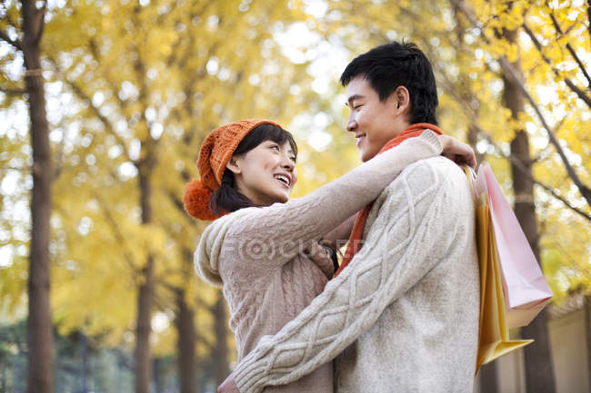 Chinese couple with shopping bags embracing in park — Stock Photo