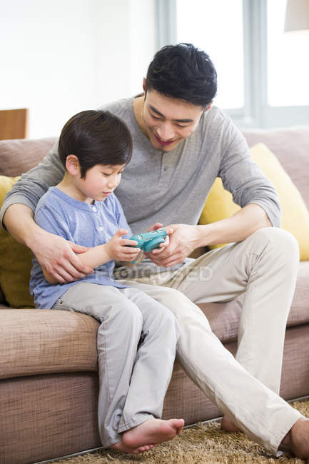 Cinese padre e figlio che giocano video gioco sul sofà — Foto stock