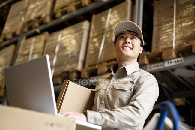 Male Chinese warehouse worker using laptop — Stock Photo