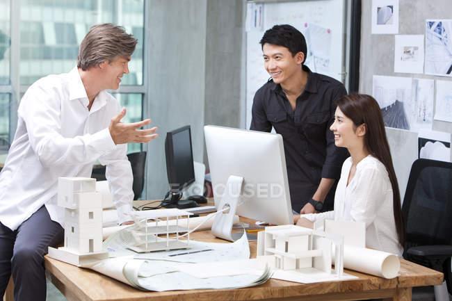 Hombre maduro y arquitectos chinos trabajando en oficina - foto de stock