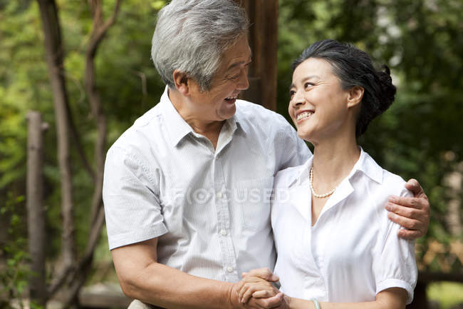 Senior Chinese couple holding hands and embracing in park — Stock Photo