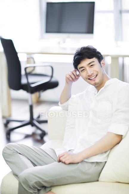 Junger chinesischer Mann sitzt auf Sofa im Wohnzimmer — Stockfoto
