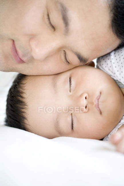 Chinese man with infant sleeping cheek to cheek, portrait — Stock Photo
