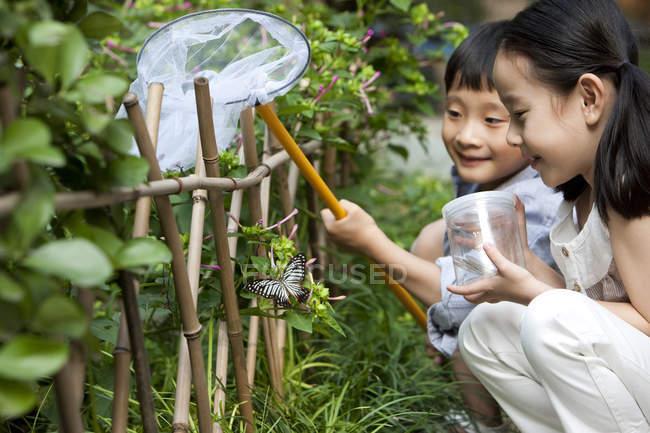 Китайские дети в саду смотрят на бабочку с сеткой для бабочек — стоковое фото
