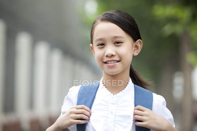 Écolière chinoise avec sac à dos à la recherche à huis clos — Photo de stock